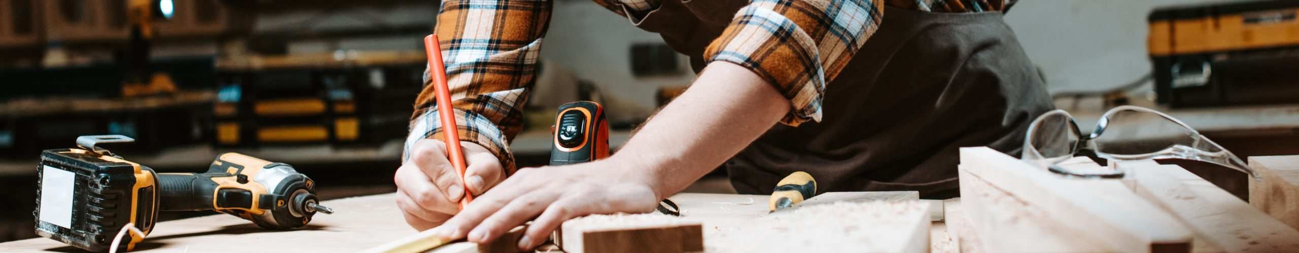 panoramic shot of woodworker measuring wooden plank
